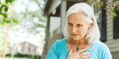 An elderly woman places her hand on her chest in pain